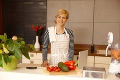 准备食物的少妇在厨房里 免版税库存图片