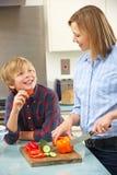 准备食物的母亲和儿子在国内厨房里 免版税库存图片