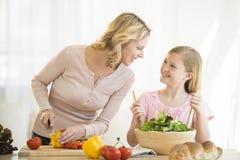 准备食物的母亲和女儿在厨房里 免版税库存图片
