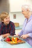 准备食物的祖母和孙子在厨房里 图库摄影