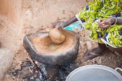准备食物的Dogon妇女使用花生酱 免版税库存照片