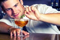 准备饮料的年轻酒吧老板 免版税库存图片