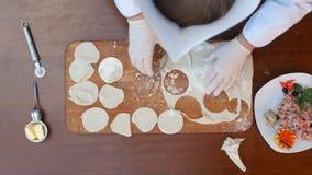 准备饺子,切面团成圈子 免版税图库摄影