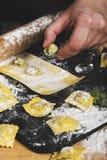 准备馄饨在有工具和成份的厨房里 免版税库存图片
