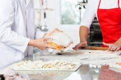 准备馄饨面团的厨师在厨台 库存照片