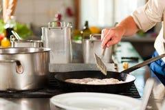 准备鱼的厨师在餐馆或旅馆厨房里 免版税库存图片