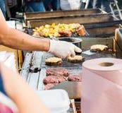 准备鲜美汉堡的厨师在室外停留演出地 免版税库存照片