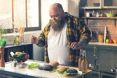 准备鲜美汉堡的男性胖子 免版税图库摄影