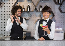 准备鸡尾酒和担任在酒吧柜台的两位侍酒者 免版税库存图片