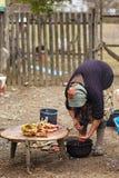 准备鸡的资深农村妇女室外 免版税库存照片