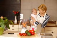 准备婴儿食品的年轻母亲 库存图片