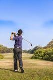 准备从发球区域箱子的高尔夫球的男性高尔夫球运动员 免版税图库摄影