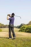 准备从发球区域箱子的高尔夫球的男性高尔夫球运动员 免版税库存照片