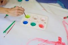 准备水彩的妇女手对绘 免版税库存照片