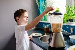准备水果鸡尾酒的愉快的孩子在厨房里 免版税库存图片
