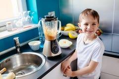 准备水果鸡尾酒的愉快的孩子在厨房里 库存照片