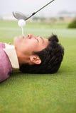 准备从说谎的人嘴的高尔夫球运动员 免版税图库摄影