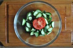 准备素食沙拉、一个碗菜蕃茄和黄瓜,顶视图 免版税库存图片