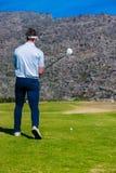 准备从高尔夫球发球区域的观点的高尔夫球运动员 库存图片