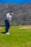 准备从高尔夫球发球区域的观点的高尔夫球运动员 免版税图库摄影