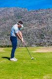 准备从高尔夫球发球区域的观点的高尔夫球运动员 图库摄影