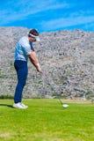 准备从高尔夫球发球区域的观点的高尔夫球运动员 免版税库存照片