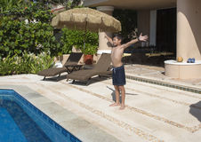 准备Amerasian的男孩跳跃在游泳池 免版税库存照片