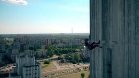 准确男性运动员下降在垂悬在高摩天大楼房子的绳索下 股票录像