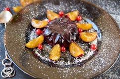 凉快的伯根地果冻用莓果和粉末装饰用新鲜的李子、红浆果和银葡萄酒匙子在棕色玻璃板 免版税库存照片