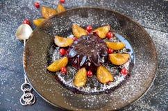 凉快的伯根地果冻用莓果和粉末装饰用新鲜的李子,红浆果和生来有福在棕色玻璃板关闭 免版税库存图片