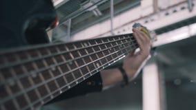 凉快的在党的表现的期间特写镜头低音吉他弹奏者 串和低音演奏员的手的特写镜头 股票录像