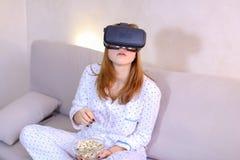 凉快的女孩观看在VR玻璃的录影,坐在brigh的长沙发 免版税库存图片
