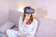 凉快的女孩观看在VR玻璃的录影,坐在brigh的长沙发 库存图片