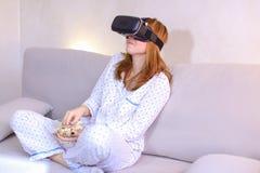 凉快的女孩观看在VR玻璃的录影,坐在brigh的长沙发 免版税库存照片