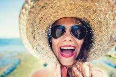 凉快的女孩,使用与在海滩的帽子的少妇在一个夏天晴天 免版税库存图片