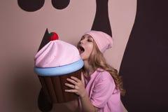 凉快的年轻白肤金发的妇女尖酸的大杯形蛋糕甜点装饰 库存照片