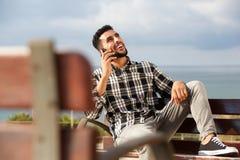 凉快的年轻阿拉伯人谈话在手机户外 免版税图库摄影