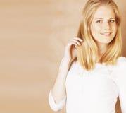 年轻凉快的弄乱了她的头发微笑紧密在温暖的棕色背景,生活方式人概念的blong十几岁的女孩 免版税库存照片