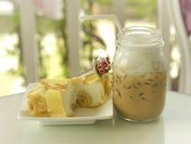 凉快的甜香蕉绉纱蛋糕用在玻璃瓶的冰冻咖啡 免版税库存图片