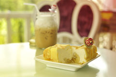 凉快的甜香蕉绉纱蛋糕用在玻璃瓶的冰冻咖啡 免版税库存照片