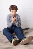 凉快的男孩坐他的滑板,拿着智能手机 库存图片