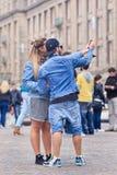 凉快的穿戴的夫妇采取在水坝正方形,阿姆斯特丹,荷兰的selfie 免版税库存照片