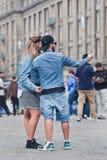 凉快的穿戴的夫妇采取在水坝正方形,阿姆斯特丹,荷兰的selfie 库存照片