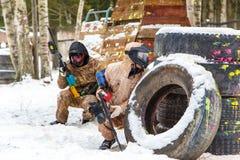 凉快的迷彩漆弹运动在冬天 在设防后的两位射击者 库存照片