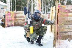 凉快的迷彩漆弹运动在冬天 在设防后的两位射击者 图库摄影