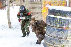 凉快的迷彩漆弹运动在冬天 在设防后的两位射击者 免版税库存照片
