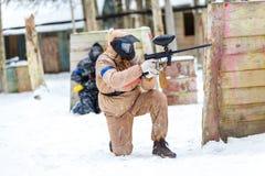 凉快的迷彩漆弹运动在冬天 在设防后的两位射击者 免版税库存图片