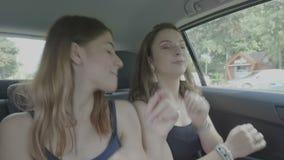 凉快的青少年的女孩坐乘坐的汽车跳舞后座在音乐节奏的在旅行期间- 股票录像