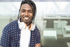 凉快的非裔美国人的人画象在有音乐耳机和微笑的城市,积极态度 免版税图库摄影