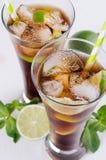 凉快的鸡尾酒兰姆酒和可乐在玻璃与泡影和冰块,石灰,薄菏在柔光白色背景,顶视图,特写镜头中 免版税库存照片